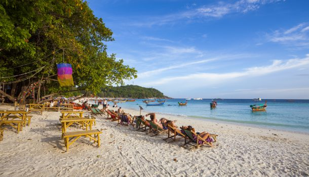 Satun, Thailand - March 12, 2011: People sunbathing in the shores of Koh Lipe beach in Satun, Thailand. Traditional longtail boats can be seen in the background.
