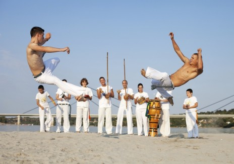 Group of people performing capoeira on the beach.