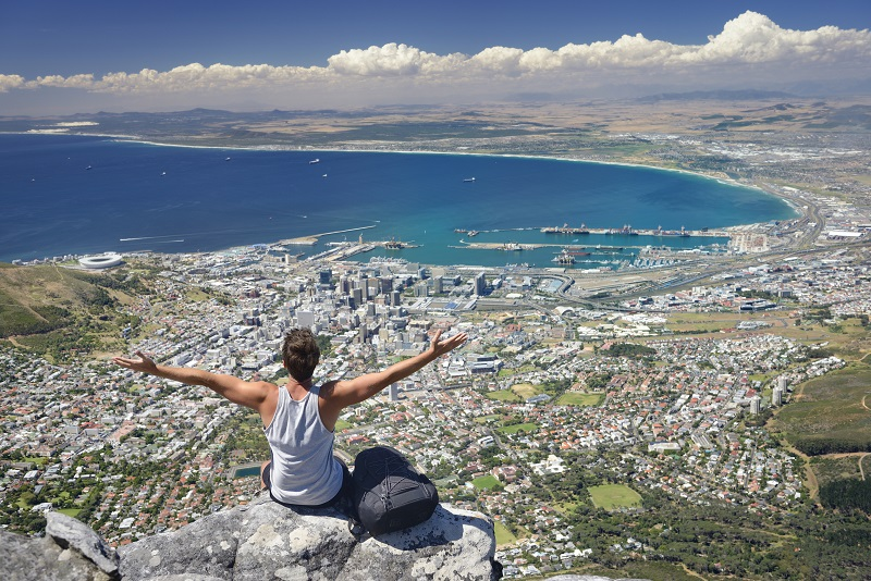 Tourist Hiker on Table Mountain overlooking Cape Town, South Africa. You can see the Cape Town Stadium on the left beside the Victoria and Alfred Waterfront. Down Town Cape Town, the Harbor all the way over Bloubergstrand to Atlantis.