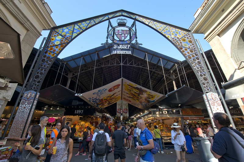 Barcelona, Spain - June 26, 2015: Tourists in famous La Boqueria market on June 26, 2015 in Barcelona. One of the oldest markets in Europe that still exist.