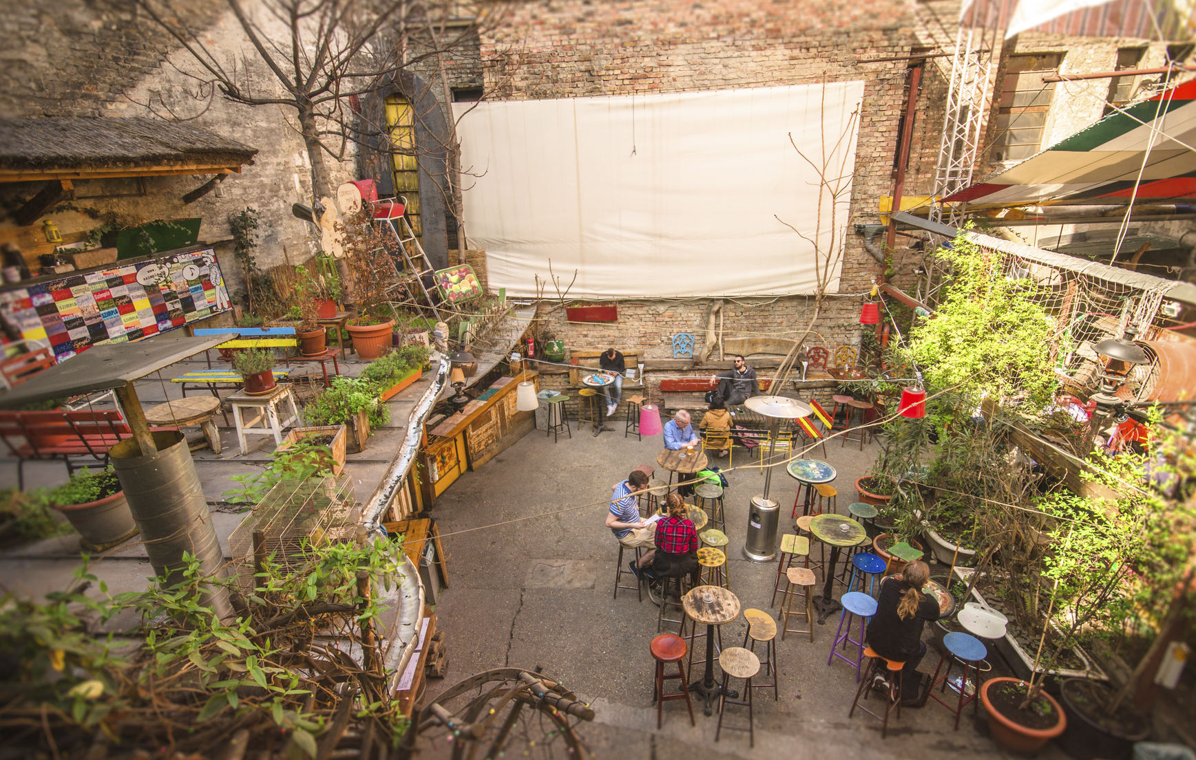 Budapest, Hungary - Mars 31, 2016: Outdoor terrace of one of the most attractive and touristic ruin pubs, the Szimpla, at Kazinczy street. Ruin pubs, most in District VII, former Jewish quarter, are a trend of Budapest cultural and night life.